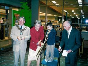 Young boy standing on a chair cuts ribbon with giant scissors while 2 men and one women look on at the grand reopening of the Petawawa Public Library in 2004.