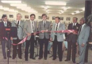 Seven men hold a long pink ribbon as the man in the middle prepares to cut it to officially open the Petawawa Public Library.