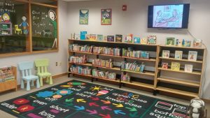 Photo of the Children's Department featuring a low bookshelf, a colourful mat and two child-sized chairs.