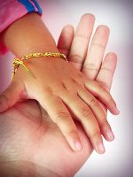 Child's hand resting in adult's hand